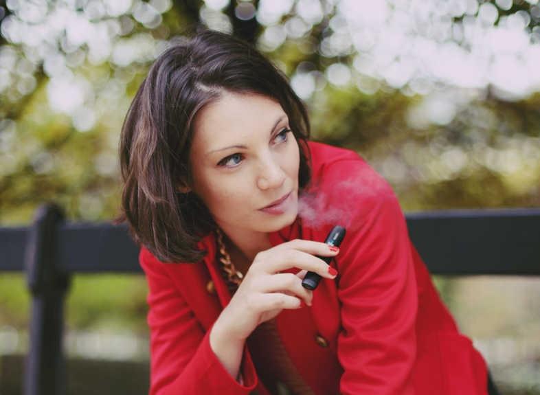 Mädchen raucht leise in dem Wissen, dass Dampfen Sie nicht fett macht