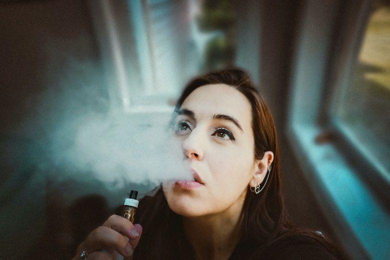 Mädchen, das elektronische Zigarette für Wangenschuss verwendet