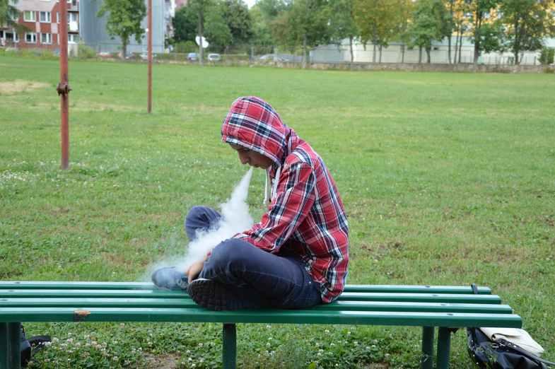 Mann, der E-Zigarettenflüssigkeiten verdampft