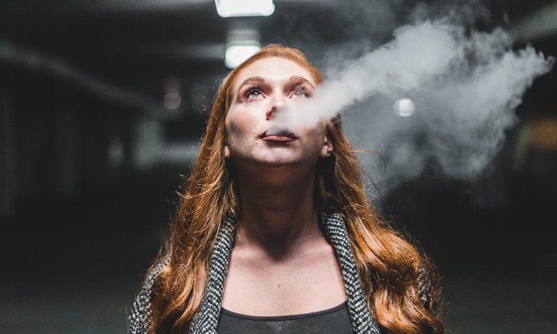 Femme vapotant avec une zigarette électronique