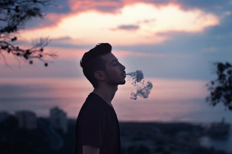 Junge raucht E-Zigarette fern von Kindern
