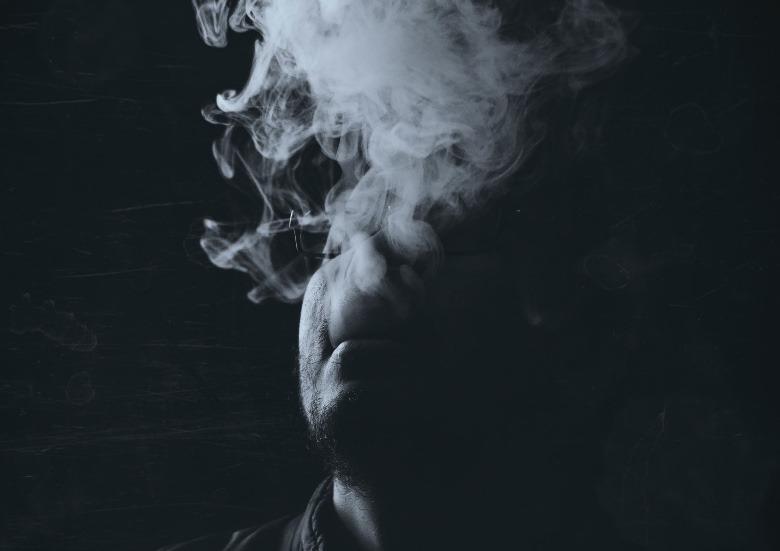 Person, die in Innenräumen dampft und Dampf aus dritter Hand produziert