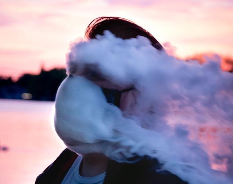 Junge, der dampft, nachdem er die Ringe seiner E-Zigarette ersetzt hat